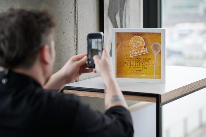 Daniel Gottschlich beim Fotografieren seiner Auszeichnung